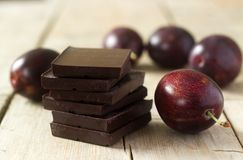 堆巧克力切片和李子在一张木桌上 土气样式,选择聚焦 免版税库存照片