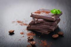 堆巧克力大块用在黑暗的石背景的薄菏用可可粉,特写镜头 库存图片