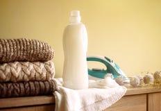 堆布料、铁和空白白色洗涤剂瓶在木桌上 图库摄影