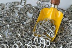 堆希望开罐头用具或延伸圈与黄色微型铁锹  库存照片