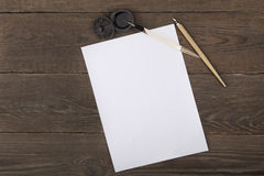 堆干净的纸,一个减速火箭的墨水池有贷方和老笔杆笔的在一张木桌上 在视图之上 库存图片
