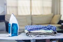 堆干净的衣裳和电熨斗在船上 免版税库存照片