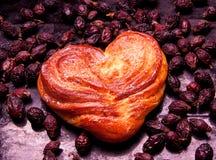 堆干野玫瑰果和核桃 以心脏的形式酵母甜小圆面包 国家家庭风格 被证实的 免版税库存照片