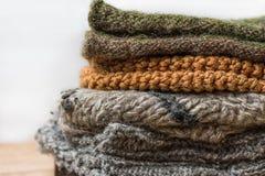 堆手工制造温暖从概略的毛纱布朗米黄灰色的被编织的袜子围巾手套在木表上 关闭 Eco方式 免版税库存照片