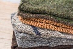 堆手工编织的温暖的冬天殴打从粗糙的毛纱布朗米黄灰色的围巾手套 免版税库存照片
