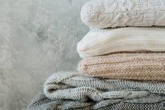 堆折叠了舒适被编织的格子花呢披肩枕头家庭装饰 免版税库存照片