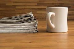 堆报纸和一杯在一张木桌上 图库摄影