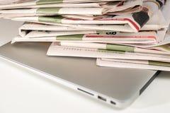 堆报纸和膝上型计算机 免版税库存图片