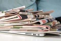 堆报纸和膝上型计算机 免版税库存照片