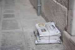 堆报纸,栓与串 在路面的星期六在一条街道在威尼斯,意大利 免版税库存照片