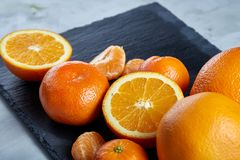堆整个和半裁减新鲜的蜜桔和桔子在切板,特写镜头 免版税库存图片