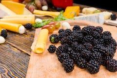 堆新鲜的黑莓用被分类的乳酪 免版税库存照片