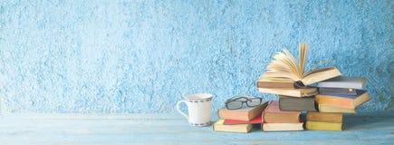 堆旧书、开放书、玻璃和一杯咖啡 库存图片