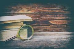 堆旧书和一个放大器在木背景与空间文本的 图库摄影