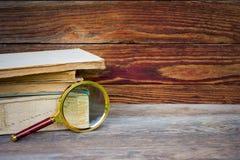 堆旧书和放大器在木背景 免版税库存图片