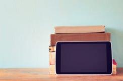 堆旧书和片剂在木架子 概念新技术 夏令时 免版税库存照片