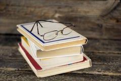 堆旧书和玻璃在木背景 库存图片