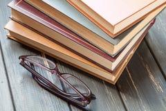堆旧书和玻璃读的 免版税库存图片
