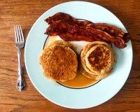 堆早餐薄煎饼,糖浆,咸肉条,在有叉子的一块板材 库存图片