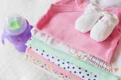 堆有一个哺乳瓶的婴孩衣物 免版税库存照片
