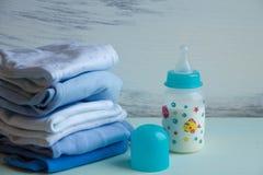 堆有哺乳瓶的婴孩衣物 免版税库存图片