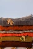 堆有秋叶的羊毛衣物 免版税库存照片