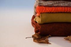 堆有秋叶的羊毛衣物 免版税库存图片