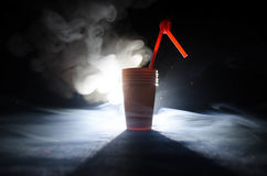 堆有秸杆的橙色塑料杯子在黑暗的背景 库存图片