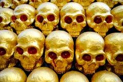 堆有红色眼睛的金黄头骨。特写镜头 图库摄影