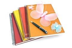 堆有蝴蝶和pe的螺纹笔记本 免版税库存照片