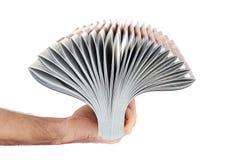堆杂志在手中被隔绝在白色 免版税库存照片