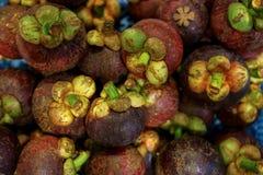 堆果子的新鲜的紫色山竹果树或女王/王后在卖在地方市场上的深刻的带红色紫色颜色的 免版税库存照片