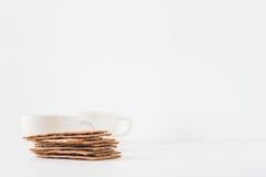 堆棕色与两个杯子的黑麦酥脆面包瑞典薄脆饼干在与空间的白色背景文本的 免版税库存照片