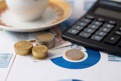 堆欧洲硬币、计算器和咖啡杯 库存图片