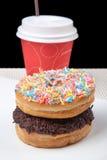堆油炸圈饼和咖啡在白色板材有黑背景 免版税库存图片