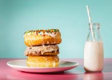 堆油炸圈饼用在瓶子的牛奶 免版税库存照片