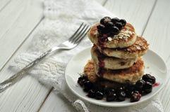 堆油煎的乳酪薄煎饼用莓果和在一张白色亚麻布餐巾的一把叉子 免版税库存图片