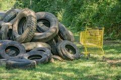 堆泥泞的轮胎和在清洁事件以后收集的杂货推车 免版税库存照片