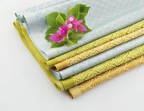 堆泰国织品和九重葛花 免版税库存图片