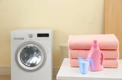堆清洁毛巾和洗涤剂在桌上在洗衣房 免版税图库摄影