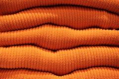 堆温暖的橙色被编织的毛线衣连续 免版税图库摄影