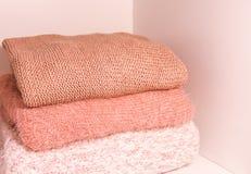 堆温暖的秋天和冬天编织了在一个家庭衣橱架子的毛线衣 现代时尚衣裳在居住的珊瑚树荫下  库存照片