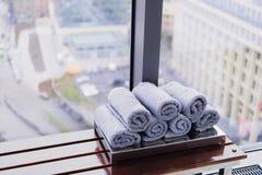 堆滚动的毛巾在健身房的旅馆里有城市视图 免版税库存照片