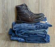 堆牛仔裤和起动 库存照片