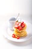 堆甜薄煎饼用草莓和蜂蜜 图库摄影