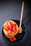 堆甜薄煎饼用草莓和蜂蜜 库存照片