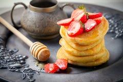 堆甜薄煎饼用草莓和蜂蜜 库存图片