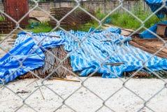 堆生锈的钢筋在建造场所通过金属滤网篱芭 图库摄影