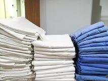 堆白色和蓝色布料,毛巾,床罩,床单在医院,有迷离白色背景 免版税库存照片