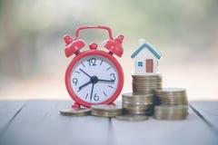 堆的微型房子硬币、金钱和房子、抵押,储款金钱购买房子的和贷款对商业投资真的 库存照片